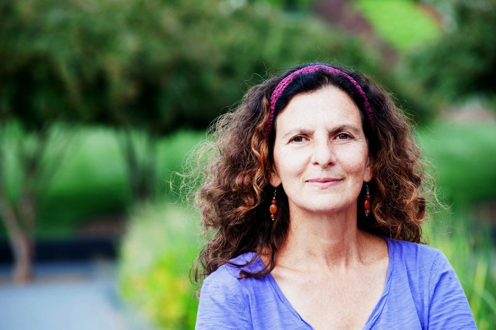 Image: Photo of Author, Poet, Dancer, and Teacher Cheryl Pallant. Ms. Pallant is facing the camera, smiling. She is wearing a purple shirt, her hair long, wavy, and flowing. In the background, a beautiful, green, natural setting.