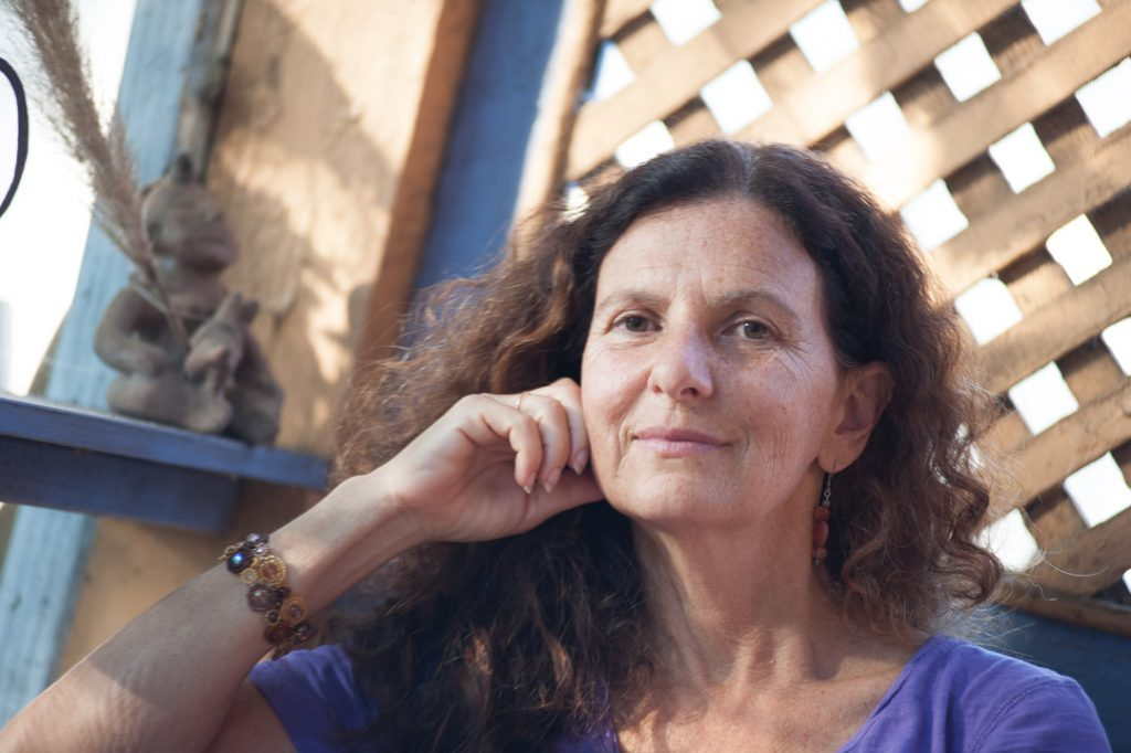 Image of author, poet, teacher, and dancer Cheryl Pallant. She is facing the camera, smiling.