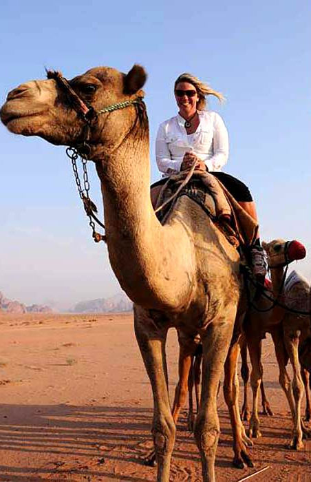 Photo of award-winning author K.J. Howe riding a racing camel in Jordan. Photo credit: K.J. Howe