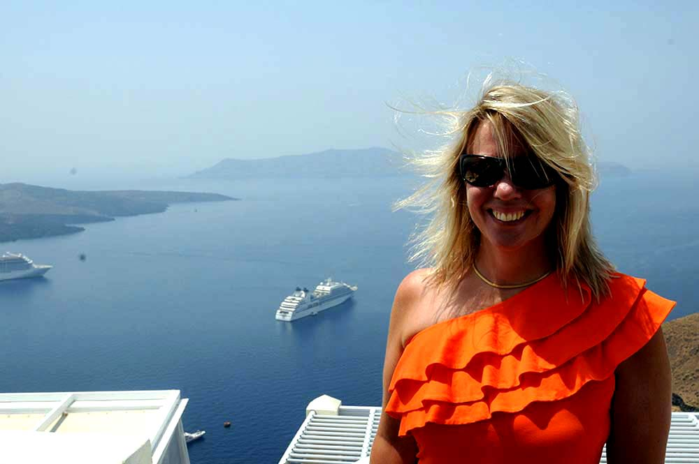 Award-winning thriller author K.J. Howe, creator of the Thea Paris series.   A photo of Ms. Howe in Santorini, wearing an orange shirt. She is standing to the right of the frame, with the Aegean Sea behind her and a yacht off in the distance.