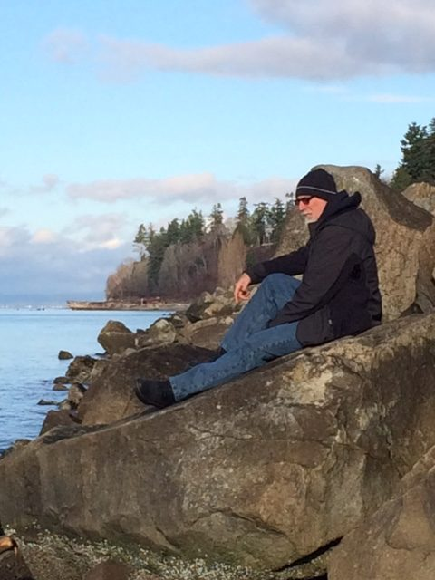 Dr. Mark Seely, author of Stones: Meditations on Human Authenticity, sitting on a rock at Point Beach
