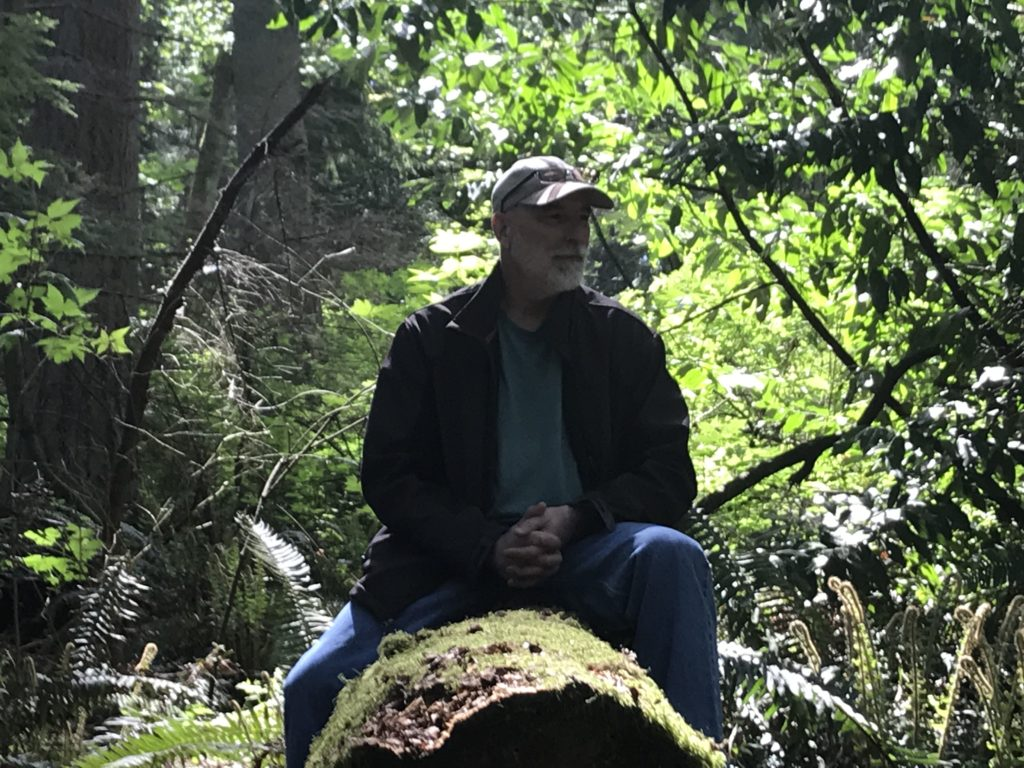 Dr. Mark Seely, author of Stones: Meditations on Human Authenticity, sitting on a log in Southwest County Park
